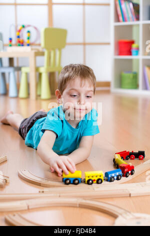 Child boy playing with wooden railway on the floor - Stock Photo