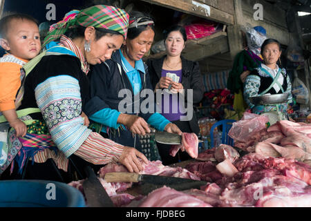 Hmong women buy meat and offal at a market in the northern Vietnam village of Ta Giang Phing. - Stock Photo