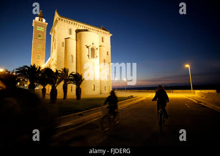 Two cyclist pass St. Nicholas the Pilgrim Cathedral, Trani, Bari Province, Puglia, Italy at night - Stock Photo