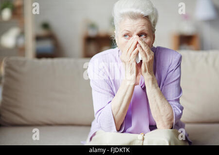 Sad senior woman sitting on sofa and crying - Stock Photo