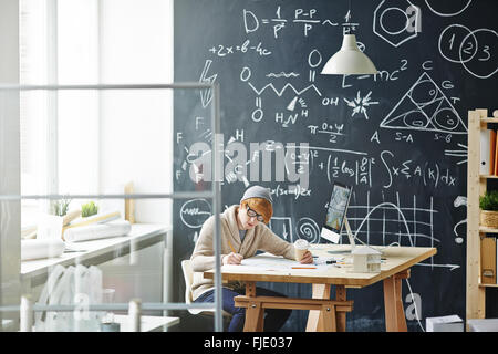 Young man sitting at the desk and doing his homework - Stock Photo