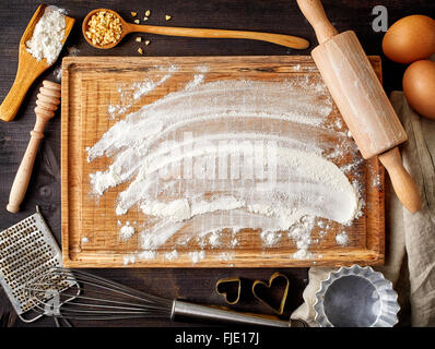 Baking background with cutting board, eggs, sugar, flour, rolling pin, grater and spoons, top view - Stock Photo