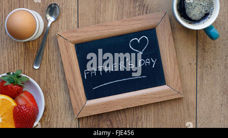 Father's day written on a chalkboard between a breakfast for him - Stock Photo