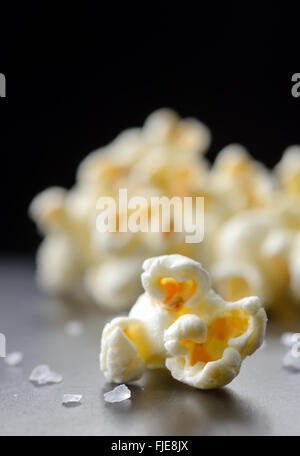 Popcorn and salt isolated on black background - Stock Photo