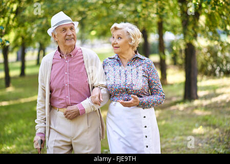 Family of two walking in the park in summer - Stock Photo
