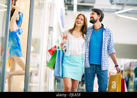 Woman showing something to her boyfriend in the shopping mall - Stock Photo