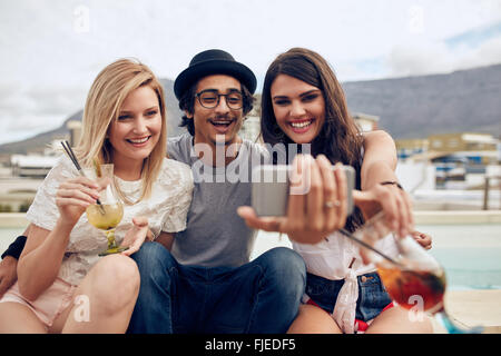 Group of friends taking selfie on a smart phone. Young man and women with drinks taking a self portrait on cell - Stock Photo