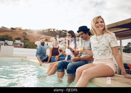 Multi-ethnic group of young people hanging out by swimming pool holding cocktails. Happy friends enjoying party - Stock Photo
