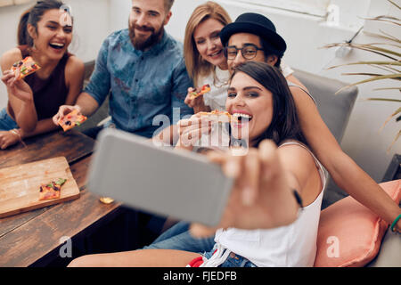 Group of multiracial young people taking a selfie while eating pizza. Young woman eating pizza her friends sitting - Stock Photo
