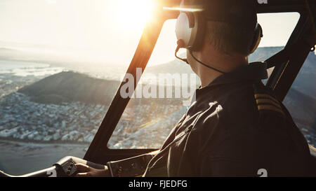 Close up of a male pilot flying a helicopter and looking outside the window with sun flare entering the cockpit. - Stock Photo