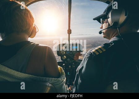 Rear view of male and female pilots flying a helicopter on sunny day. Man flying a helicopter with his copilot looking - Stock Photo