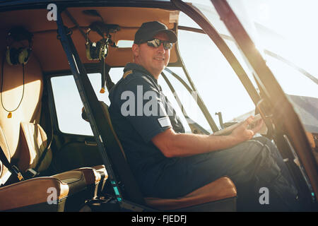 Portrait of happy male pilot sitting in the cockpit of a helicopter with a aviation map. - Stock Photo