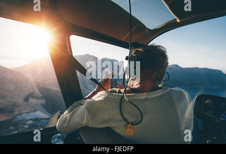 Rear view of female tourist on helicopter tour taking pictures while flying over mountains on a sunny day. - Stock Photo