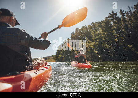 Outdoor shot of senior man canoeing in the lake with woman in background on a summer day. Man and woman in two different - Stock Photo