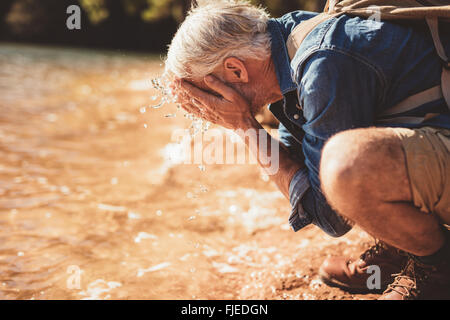 Side portrait of a mature man washing his face in the lake during a hike. Senior man with backpack sitting at the - Stock Photo