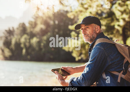 Portrait of senior man sitting near a lake with backpack and digital tablet. Mature male hiker sitting at a lake - Stock Photo