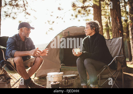 Mature man and woman sitting and talking at a campsite. Senior couple sitting in chairs outside the tent on a summer - Stock Photo