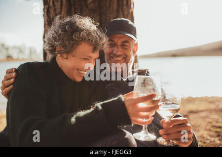 Portrait of relaxed mature couple having a glass of wine at campsite. Senior man and woman toasting wine at on summer - Stock Photo