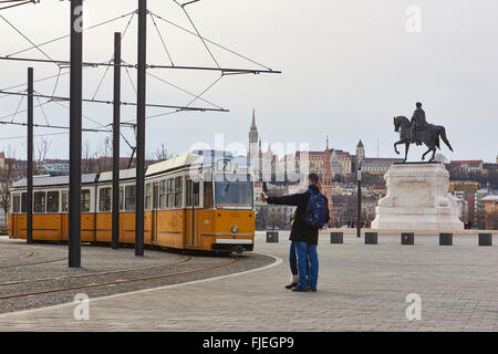 BUDAPEST, HUNGARY - FEBRUARY 02: Young couple taking selfie next to tram line number two near Hungarian Parliament - Stock Photo