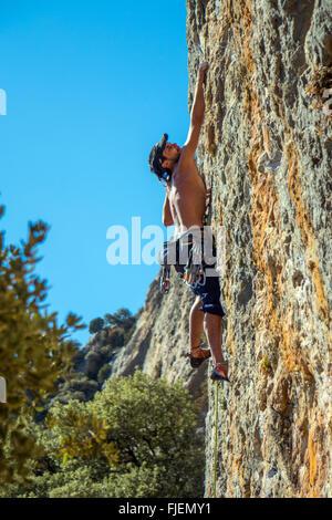 Male rock climber on steep limestone cliff Spain - Stock Photo