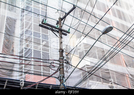 power lines on electric pole in front of a building under construction - Stock Photo