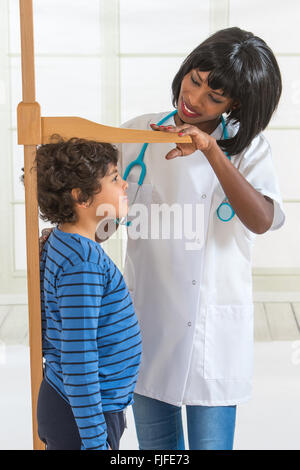 Doctor Measuring Height of Little Boy on Traditional Medical Scale - Stock Photo