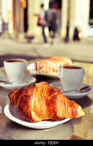 closeup of a table in the terrace of a cafe set for breakfast, with some cups of coffee, a croissant and a spanish - Stock Photo