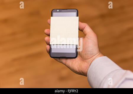 Human hand holding a smartphone with blank yellow note sticked on it. - Stock Photo