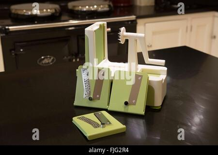 Brand new spiralizer with its different blades sitting on a country cottage kitchen work top in front of a black - Stock Photo