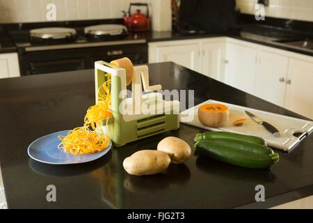 Making courgette noodles or 'courgetti' in a family kitchen using a spiralizer with other vegetables - Stock Photo