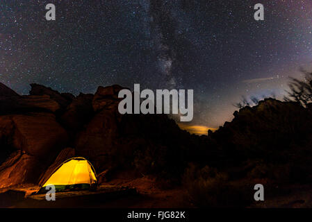 Tent on a campsite with starry sky above and Milky Way, night scene, Wildrose Campground, Death Valley National Park, California