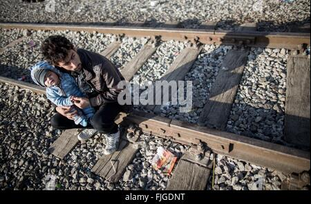 Idomeni, Greece. 02nd Mar, 2016. A refugee from Iraq sits with his baby on the tracks and waits at the Greek-Macedonian - Stock Photo