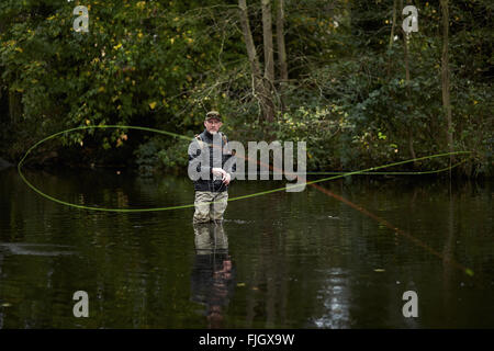 A man fly fishing in a river - London, UK - Stock Photo