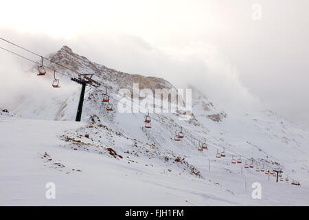 A chair lift in snow covered mountains of the Italian alps - Stock Photo