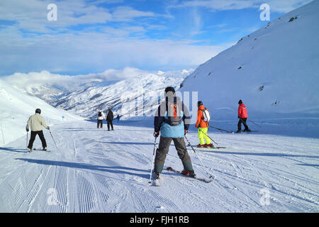 Skiing downhill in French Alps Three valleys ski resort on sunny winter day - Stock Photo