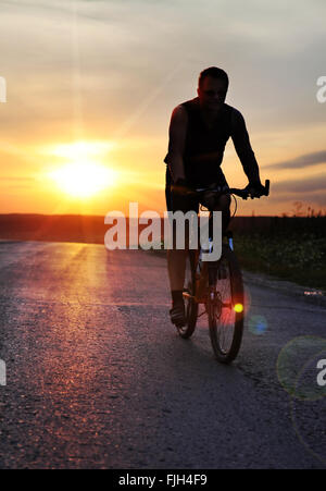traveler with bike stopped on field at sunset time - Stock Photo