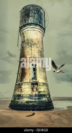 Old lighthouse on the beach with a seagull flying to it - Stock Photo