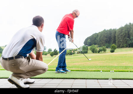 Golf trainer working with golf player on driving range - Stock Photo