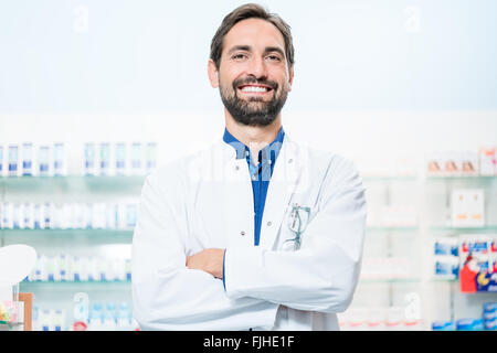Apothecary in pharmacy standing at shelf with drugs - Stock Photo