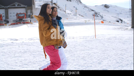 Two young women walking through snow at a resort - Stock Photo