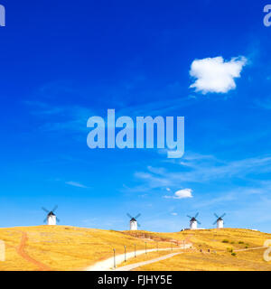 Cervantes Don Quixote windmills, rural green fields, blue sky and small cloud in Consuegra. Castile La Mancha, Spain, - Stock Photo