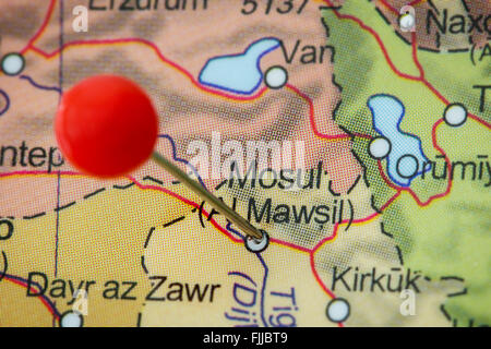 Close-up of a red pushpin in a map of Mosul, Iraq. - Stock Photo