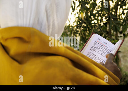 Nun reading Holy Scriptures outside the new Church of Our Lady Mary of Zion in Axum (or Aksum), Tigray Region, Ethiopia - Stock Photo