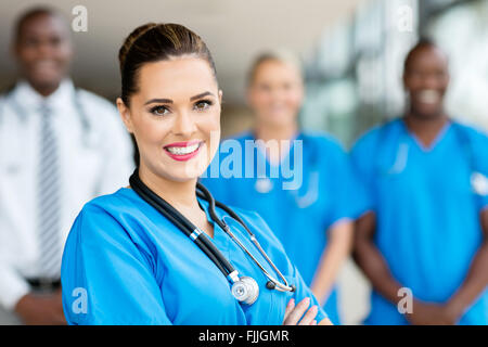 attractive young medical doctor and colleagues in hospital - Stock Photo