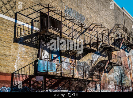 Fire escapes on the side of an industrial building/ warehouse in New York City with graffiti on the brickwork wall. - Stock Photo