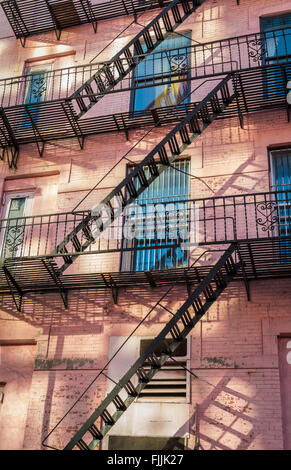 Pink old traditional building in New York City with metal fire escapes on the facade. - Stock Photo