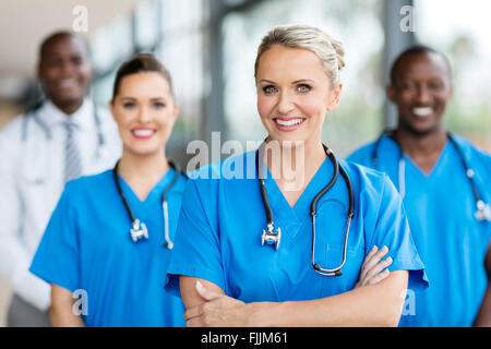 pretty female medical doctor with colleagues in background - Stock Photo