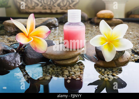 Mini set of bubble bath and shower gel decorated in zen style with pebble rock and flower with relaxing mood with - Stock Photo