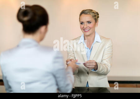 friendly hotel receptionist handing over key to customer - Stock Photo