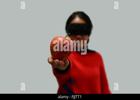 Woman blindfolded on white background and take an apple - Stock Photo